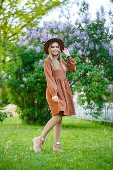 Jonge mooie vrouw die zich tegen de achtergrond van lila struiken bevindt. meisje in bruine hoed en jurk