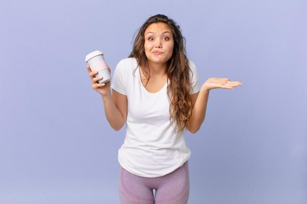 Jonge mooie vrouw die zich verbaasd en verward voelt en twijfelt en een kopje koffie vasthoudt