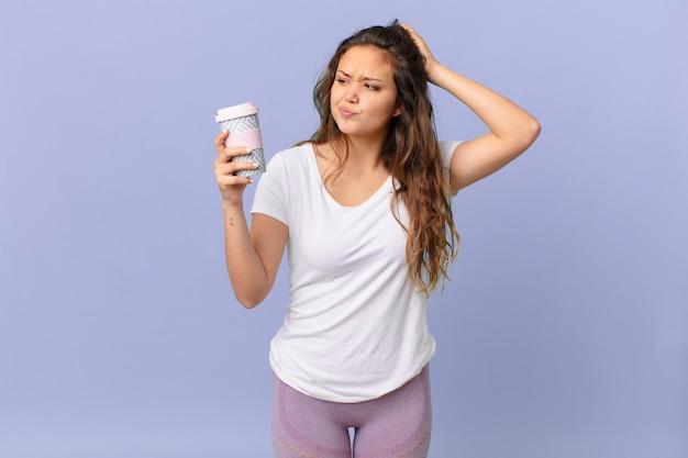 Jonge mooie vrouw die zich verbaasd en verward voelt, haar hoofd krabt en een kopje koffie vasthoudt