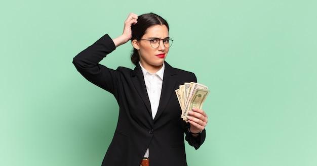 Jonge mooie vrouw die zich verbaasd en verward voelt, haar hoofd krabt en opzij kijkt. bedrijfs- en bankbiljettenconcept