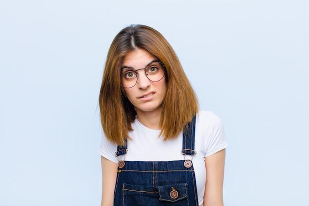 Jonge mooie vrouw die zich verbaasd en verward voelt, met een domme, verbijsterde uitdrukking die iets onverwachts over de blauwe muur bekijkt