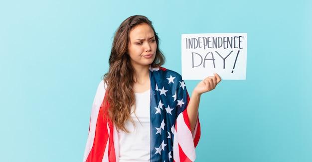 Jonge mooie vrouw die zich verdrietig, overstuur of boos voelt en naar het concept van de onafhankelijkheidsdag kijkt
