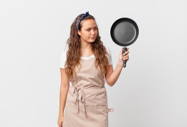 Jonge mooie vrouw die zich verdrietig, overstuur of boos voelt en naar het concept van de zijkok kijkt en een pan vasthoudt