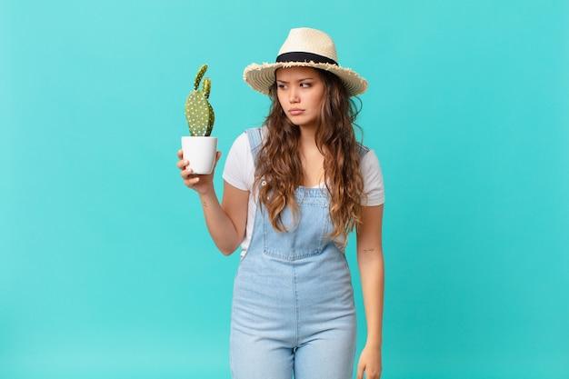 Jonge mooie vrouw die zich verdrietig, overstuur of boos voelt en opzij kijkt en een cactus vasthoudt
