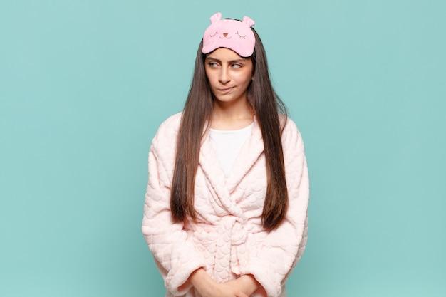 Jonge mooie vrouw die zich verdrietig, overstuur of boos voelt en opzij kijkt met een negatieve houding, fronsend in onenigheid. wakker worden met pyjama's concept