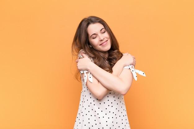 Jonge mooie vrouw die zich verliefd voelt, glimlacht, knuffelt en zichzelf knuffelt, vrijgezel blijft, egoïstisch en egocentrisch is tegen oranje muur