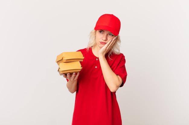 Jonge mooie vrouw die zich verveeld, gefrustreerd en slaperig voelt na een vermoeiende hamburger bezorgconcept