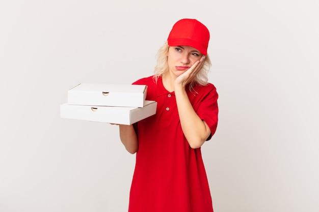 Jonge mooie vrouw die zich verveeld, gefrustreerd en slaperig voelt na een vermoeiende pizza bezorgconcept