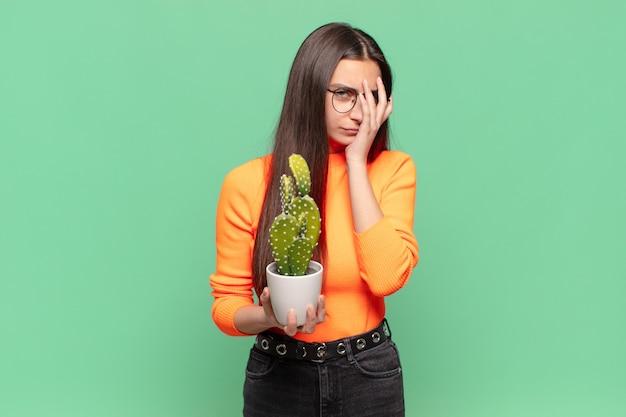 Jonge mooie vrouw die zich verveeld, gefrustreerd en slaperig voelt na een vermoeiende, saaie en vervelende taak, gezicht met de hand vasthoudend. cactusconcept