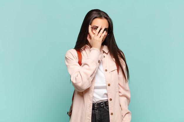 Jonge mooie vrouw die zich verveeld, gefrustreerd en slaperig voelt na een vermoeiende, saaie en vervelende taak, gezicht met de hand vasthoudend. studentenconcept