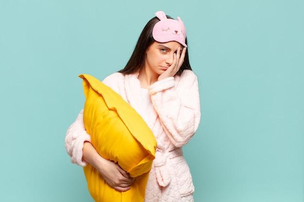 Jonge mooie vrouw die zich verveeld, gefrustreerd en slaperig voelt na een vermoeiende, saaie en vervelende taak, gezicht met de hand vasthoudend. wakker worden met pyjama's concept