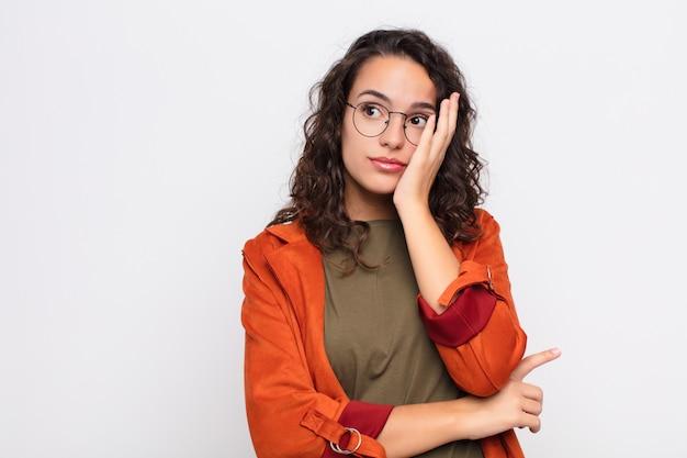Jonge mooie vrouw die zich verveeld, gefrustreerd en slaperig voelt na een vermoeiende, saaie en vervelende taak, gezicht met hand vasthoudend tegen witte muur