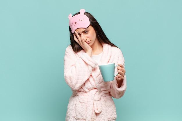 Jonge mooie vrouw die zich verveeld, gefrustreerd en slaperig voelt na een vermoeiende, saaie en vervelende taak, gezicht met hand vasthoudend