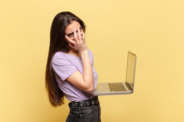 Jonge mooie vrouw die zich verveeld, gefrustreerd en slaperig voelt na een vermoeiende, saaie en vervelende taak, haar gezicht met de hand vasthoudend