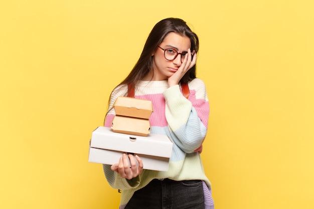 Jonge mooie vrouw die zich verveelt, gefrustreerd voelt terwijl ze een stapel boeken vasthoudt