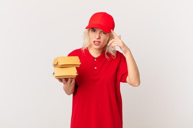 Jonge mooie vrouw die zich verward en verbaasd voelt en laat zien dat je gek bent. hamburger bezorgconcept