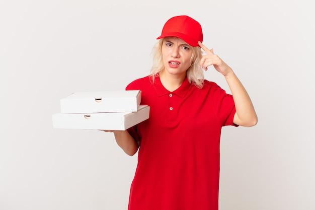 Jonge mooie vrouw die zich verward en verbaasd voelt en laat zien dat je gek bent. pizza bezorgconcept