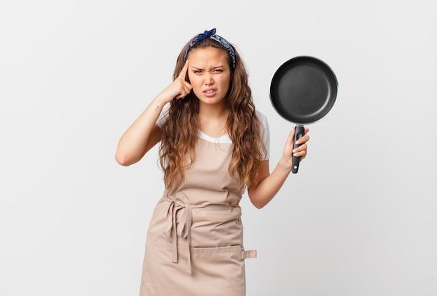 Jonge mooie vrouw die zich verward en verbaasd voelt, laat zien dat je een krankzinnig chef-kokconcept bent en een pan vasthoudt