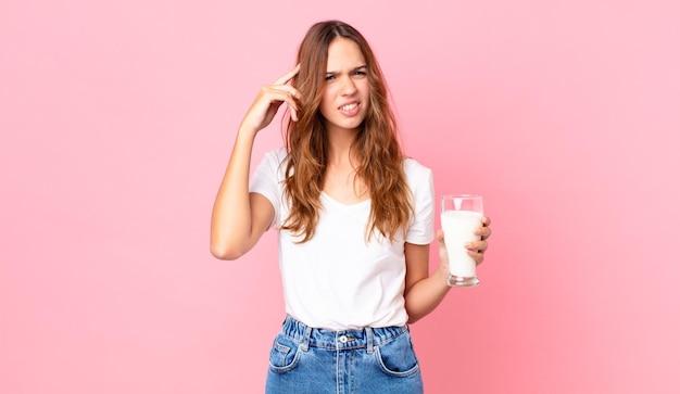 Jonge mooie vrouw die zich verward en verbaasd voelt, laat zien dat je gek bent en een glas melk vasthoudt