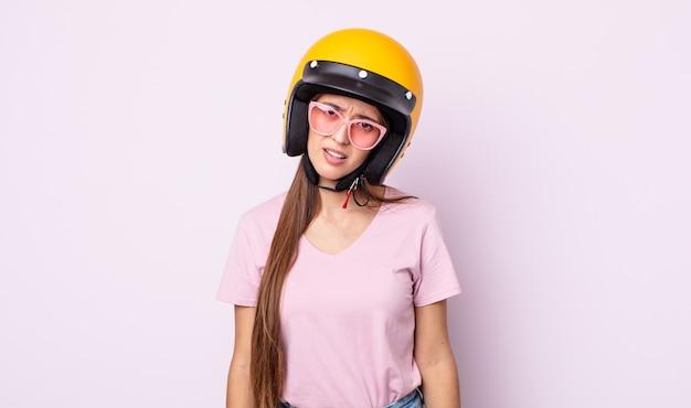 Jonge mooie vrouw die zich verward en verward voelt. motorrijder en helm
