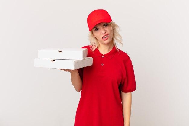 Jonge mooie vrouw die zich verward en verward voelt. pizza bezorgconcept