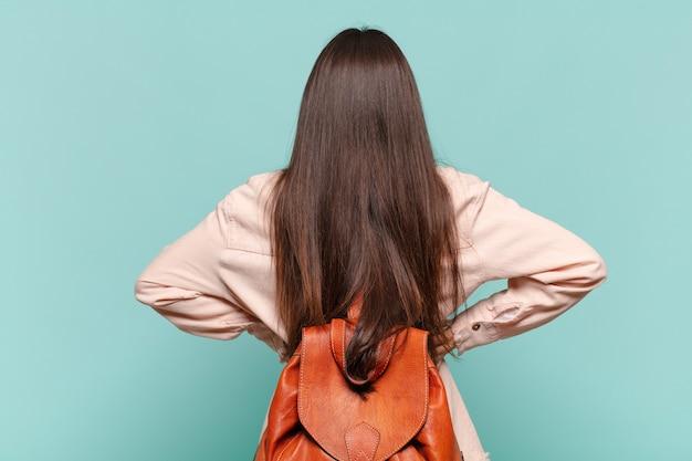 Jonge mooie vrouw die zich verward of vol voelt of twijfels en vragen, zich afvragend, met handen op de heupen, achteraanzicht. studentenconcept