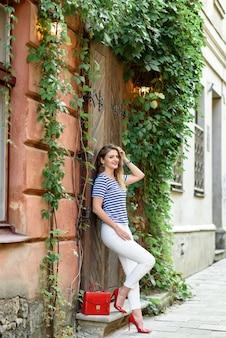 Jonge mooie vrouw die zich voordeed in de straten van de oude stad.