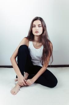 Jonge mooie vrouw die zich voordeed op een witte muur