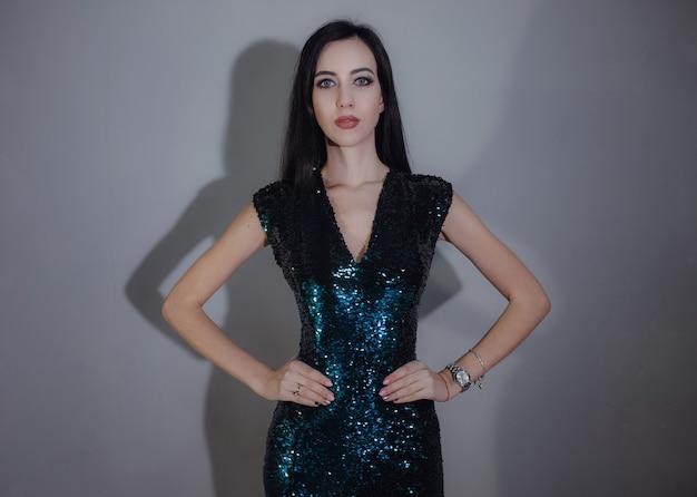 Jonge mooie vrouw die zich voordeed op grijs in verschillende jurken. kiest de beste optie voor een vakantieavond