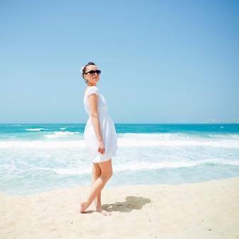Jonge mooie vrouw die zich voordeed op het strand