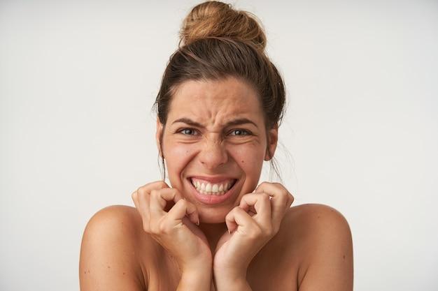 Jonge mooie vrouw die zich voordeed op wit met bang gezicht, bang hand in hand door gezicht, grimassen en tanden tonen