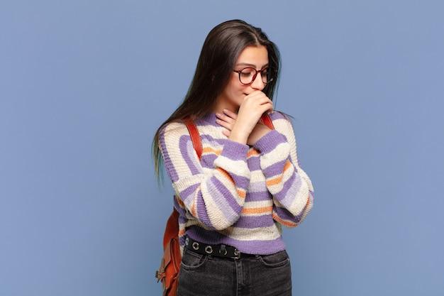 Jonge mooie vrouw die zich ziek voelt met een zere keel en griepsymptomen, hoest met bedekte mond. studentenconcept