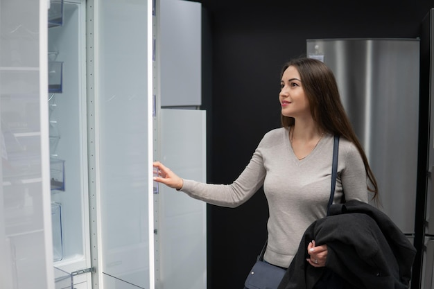 Jonge mooie vrouw die zichzelf koelkast of koelkast in een winkel supermarkt winkel vindt.