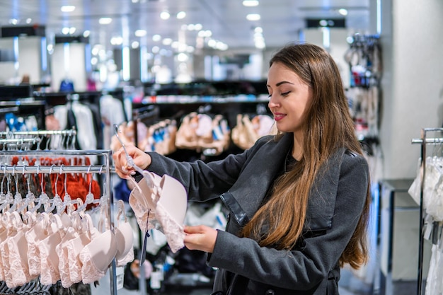 Jonge mooie vrouw die zichzelf nieuw lingerie-ondergoed vindt in het winkelcentrum van de supermarkt