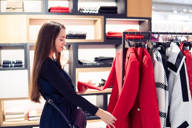 Jonge mooie vrouw die zichzelf nieuwe kleren vindt in een winkel supermarkt winkel