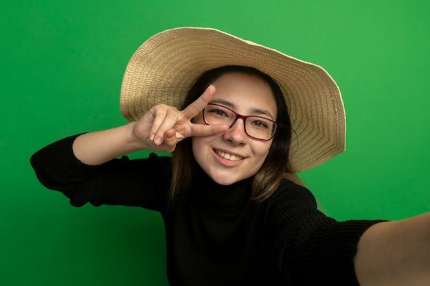 Jonge mooie vrouw die zomerhoed in een zwarte coltrui en bril draagt die aan de voorkant blij en positief glimlachend vrolijk kijkt en v-teken over groene muur maakt