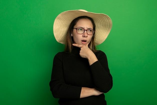 Jonge mooie vrouw die zomerhoed in een zwarte coltrui en bril draagt die opzij met hand op kin wordt verward die zich over groene muur bevindt