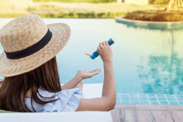 Jonge mooie vrouw die zonnescherm of zonnebrandolie in haar lichaam aanvragen voor zonnebescherming bij zwembad. donkerbruin meisje dat de zomer van vakantie geniet.