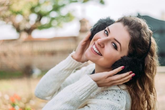 Jonge mooie vrouw die zwarte oorbeschermers en witte sweater buiten draagt.