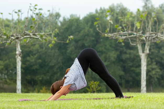 Jonge mooie vrouw doet yoga oefening buitenshuis