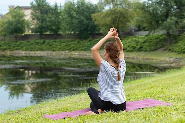 Jonge mooie vrouw doet yoga oefening in groen park. gezonde levensstijl en fitness concept.