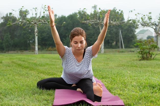 Jonge mooie vrouw doet yoga oefening in groen park