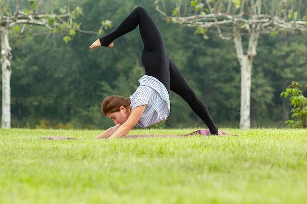 Jonge mooie vrouw doet yoga oefeningen in groen park