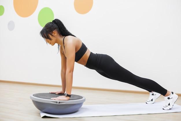 Jonge mooie vrouw doin pushups in de sportschool, fitness meisje training in de sportschool