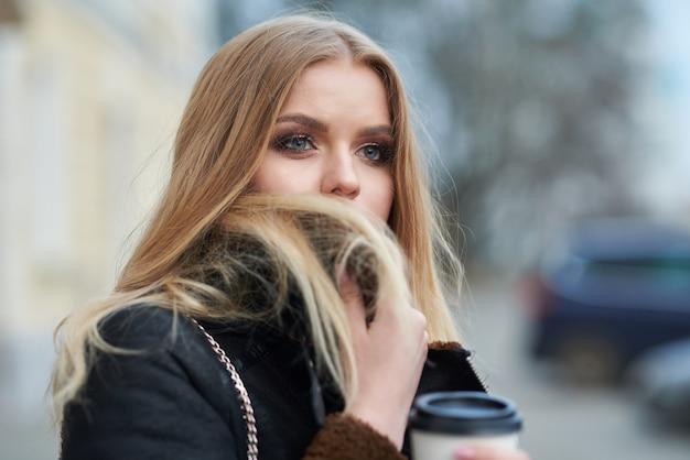 Jonge mooie vrouw drinken koffie en wandelen door de stad