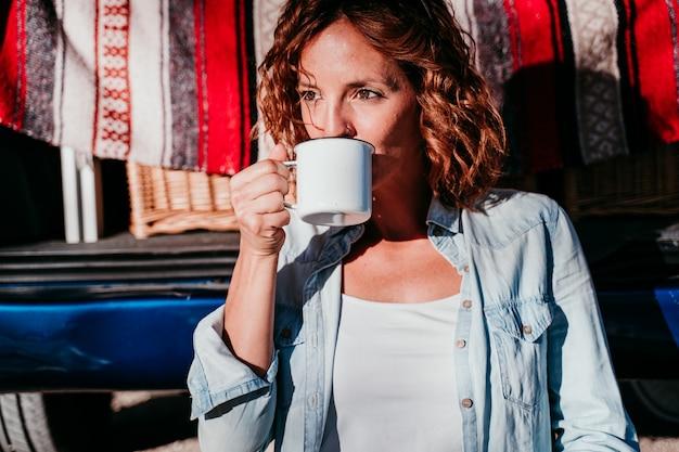 Jonge mooie vrouw drinken koffie of thee kamperen buiten met een busje en haar twee honden. reizen concept.