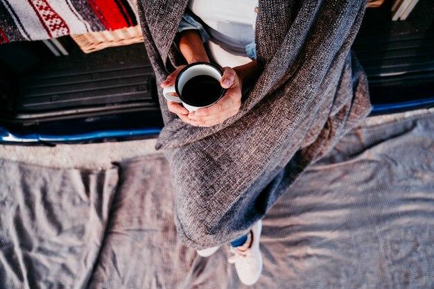 Jonge mooie vrouw drinken koffie of thee kamperen buiten met een busje. reizen concept. bovenaanzicht