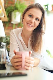 Jonge mooie vrouw, drinken koffie of thee