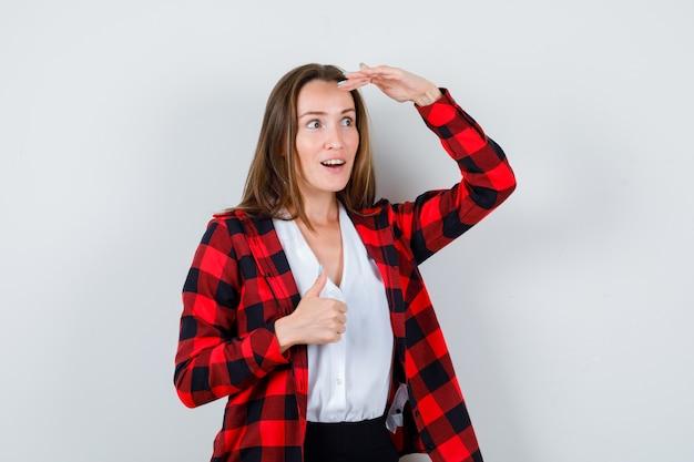 Jonge mooie vrouw duim opdagen, met de hand boven het hoofd in casual outfit en verbaasd kijken, vooraanzicht.