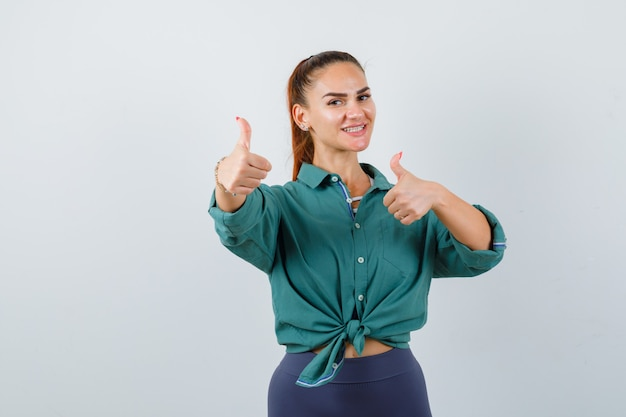 Jonge mooie vrouw duimen opdagen in groen shirt en op zoek vrolijk, vooraanzicht.